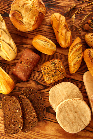 varied: Bread fresh varied mix on golden rustic wood golden table Stock Photo