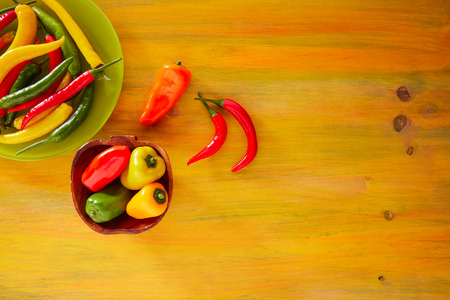 piquancy: Colorful mexican chili peppers habanero red in yellow wood background
