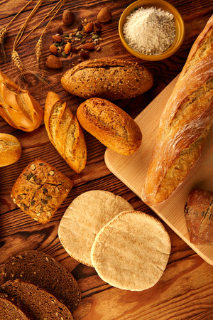 Bread fresh varied mix on golden rustic wood golden table Фото со стока