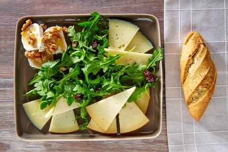 queso de cabra: Arugula mediterranean salad with goat cheese honey and nuts Foto de archivo