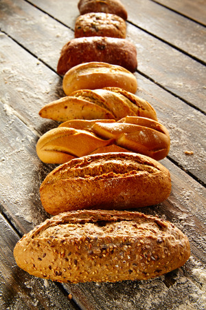 varied: Breads varied in a row on rustic wood table with wheat flour