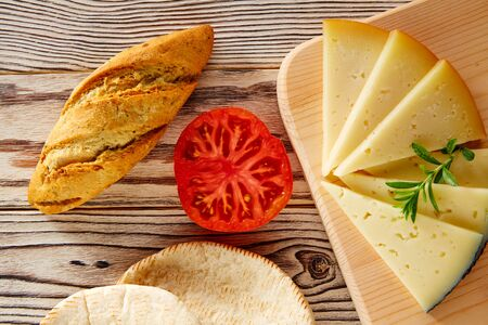 rustic food: Mediterranean food bread loaf tomatoes and cheese slices on rustic wood Stock Photo