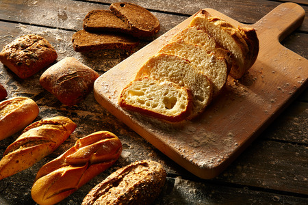 Bread varied loafs sliced on wood board in rustic wood table
