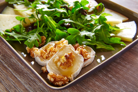 Arugula mediterranean salad with goat cheese honey and nuts Standard-Bild