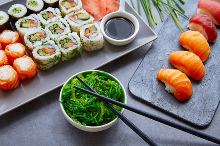 plato de comida: Sushi Maki y Niguiri California roll con salsa de soja ensalada de algas Chuka y wasabi