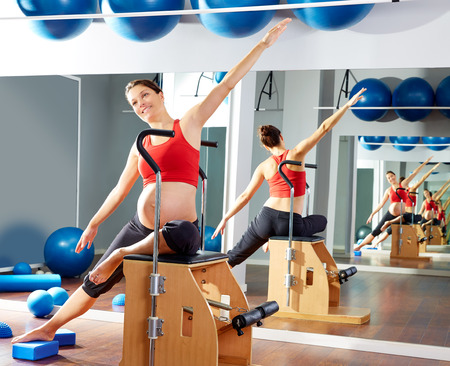 enceinte: pregnant woman pilates side stretch exercise on wunda chair at gym indoor Stock Photo