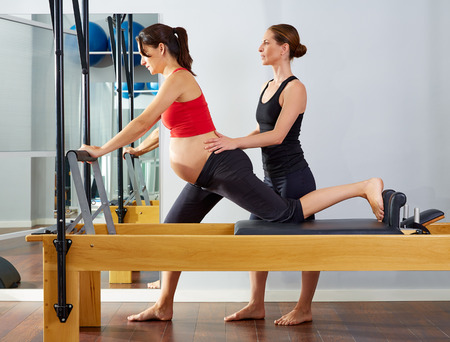 reformer: pregnant woman pilates reformer cadillac exercise workout with personal trainer