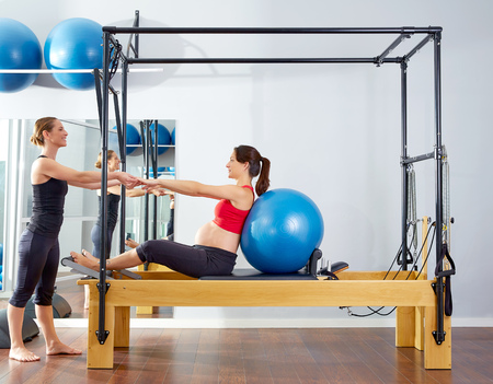 reformer: pregnant woman pilates reformer cadillac fitball exercise workout with personal trainer Stock Photo