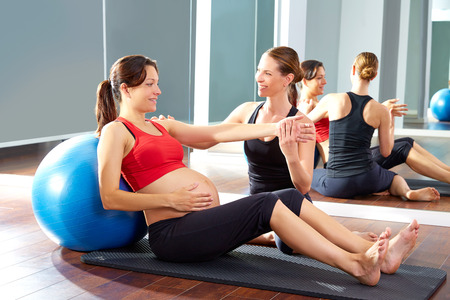 'personal beauty': pregnant woman pilates exercise fitball at gym with personal trainer