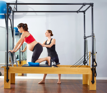 enceinte: pregnant woman pilates reformer cadillac exercise workout with personal trainer