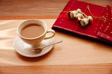 taza de té: café o té con leche que viaja con binoculares y cuaderno rojo