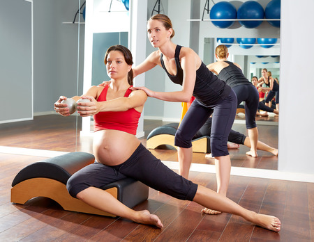'personal beauty': pregnant woman pilates side stretchs exercise workout at gym with personal trainer