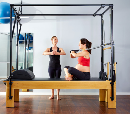 reformer: pregnant woman pilates reformer cadillac arms exercise workout with personal trainer