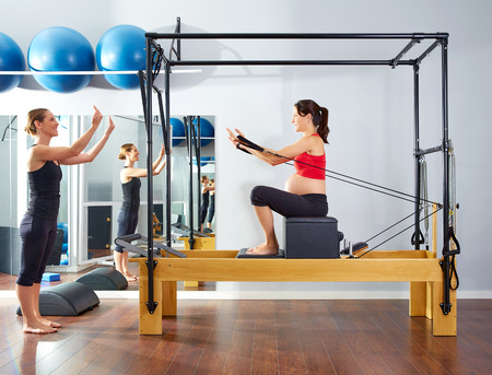 reformer: pregnant woman pilates reformer short box exercise workout with personal trainer