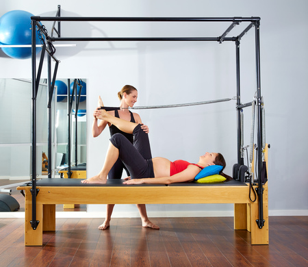 reformer: pregnant woman pilates reformer leg spring  exercise workout with personal trainer