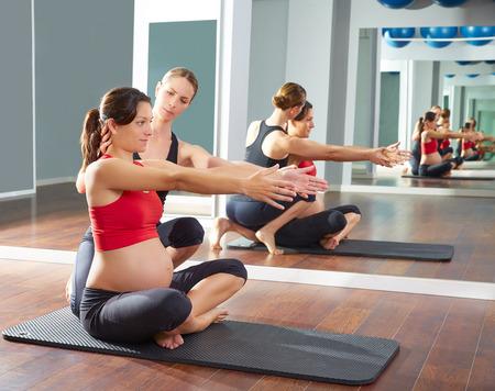 embarazadas estrenimiento: mujer embarazada pilates ejercicio ejercicios en gimnasio con entrenador personal Foto de archivo