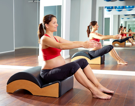 girl sport: pregnant woman pilates exercise with spine wave corrector