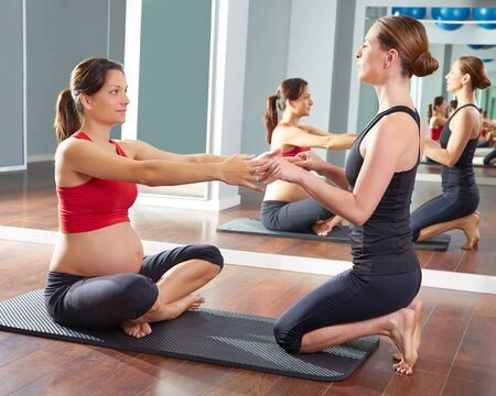 pregnant exercise: pregnant woman pilates exercise workout at gym with personal trainer Stock Photo