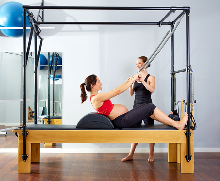 enceinte: pregnant woman pilates reformer roll up cadillac exercise with personal trainer