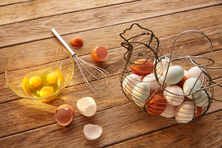 hens: Eggs in vintage hen shape basket and shaker on wood with blue easter white and brown