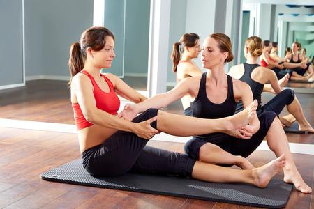 schwangere Frau Pilates-Übung trainieren im Fitnessraum mit Personal Trainer