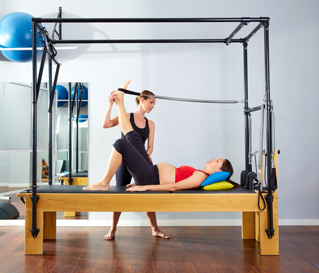 enceinte: pregnant woman pilates reformer leg spring  exercise workout with personal trainer