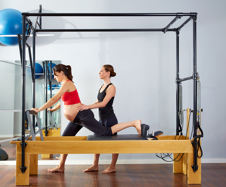personal trainer: pregnant woman pilates reformer cadillac exercise workout with personal trainer
