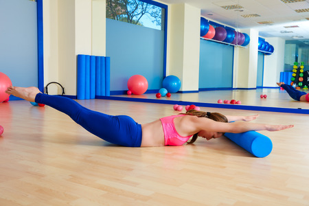 diving: Pilates woman roller swan dive roll exercise workout at gym indoor