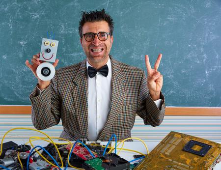 myopic: Nerd electronics technician silly teacher retro winner gesture with self made robot Stock Photo