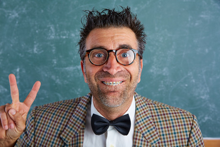 unfashionable: Nerd silly retro man teacher with braces funny expression winner victory finger gesture Stock Photo
