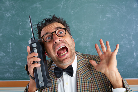 Nerd silly private investigator with retro walkie talkie on teacher balckboard