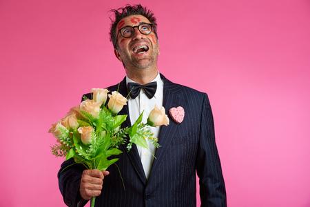 loco: Hombre del empollón con marcas de lápiz labial en la cara en el Día de San Valentín y las flores