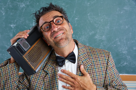 tacky: Nerd silly retro teacher man with braces and vintage radio and crazy expression Stock Photo