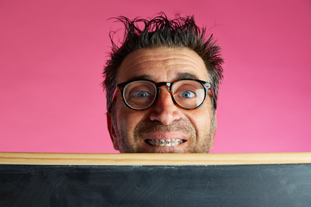 unfashionable: Nerd man crazy behind a blackboard and braces smile funny gesture in pink background Stock Photo