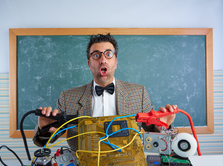 unfashionable: Nerd electronics technician retro teacher silly expression with big battery clamps in pcb Stock Photo