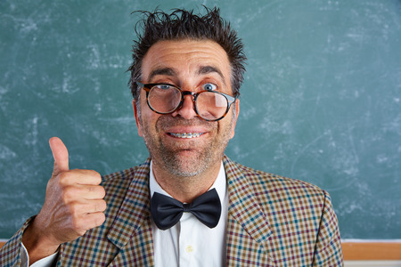 unfashionable: Nerd silly retro teacher man with braces funny expression ok thumb up gesture