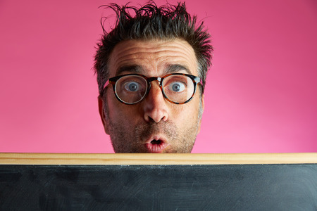 tacky: Nerd man crazy behind a blackboard funny surprise gesture in pink background