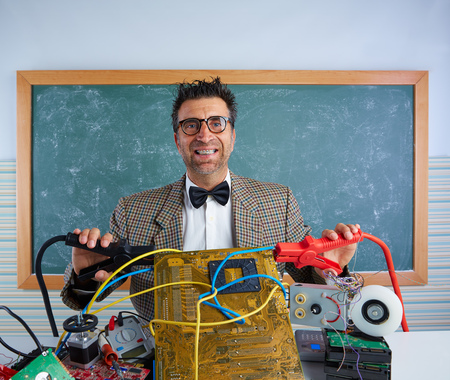 Nerd electronics technician retro teacher silly expression with big battery clamps in pcb Stock Photo