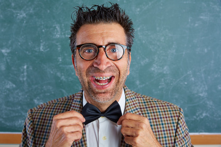 unfashionable: Nerd silly retro teacher man with braces funny expression bow tie portrait