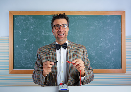 unfashionable: Nerd electronics technician retro teacher silly expression working tester pins Stock Photo