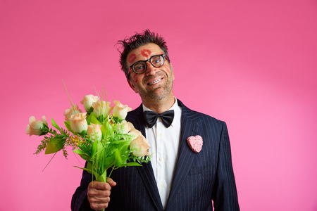 tacky: Nerd man with lipstick marks on face in Valentines Day and flowers