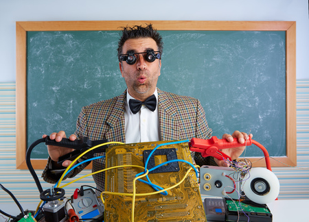 myopic: Nerd electronics technician retro teacher silly expression with big battery clamps in pcb Stock Photo