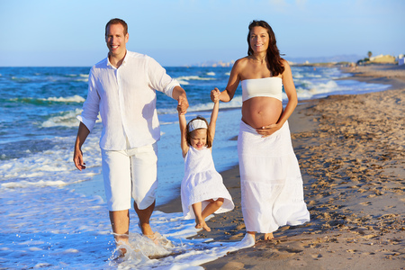 enceinte: Happy family on the beach sand walking with pregnant mother woman