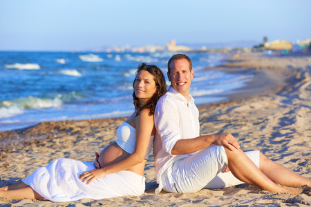 enceinte: Beautiful couple pregnant woman in the beach sitting on sand happy together back to back