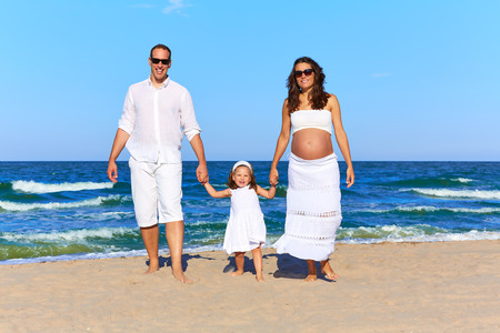enceinte: Happy family on the beach sand walking pregnant mother woman Stock Photo