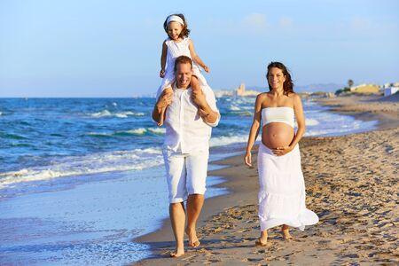 mom dad: Familia feliz en la playa de arena de caminar con la mujer madre embarazada Foto de archivo