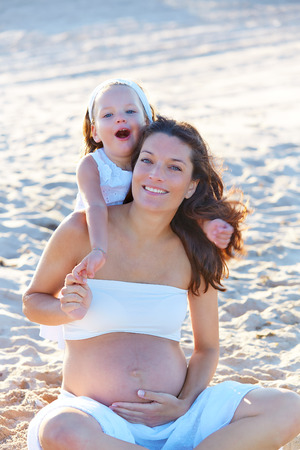 enceinte: Pregnant mother and daughter on the beach together hug sitting on sand