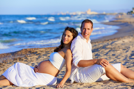 mommy: Beautiful couple pregnant woman in the beach sitting on sand happy together back to back