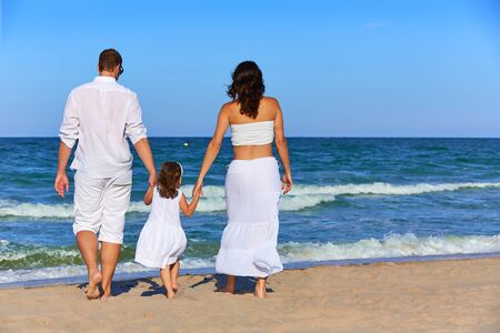 enceinte: Happy family on the beach sand walking rear back view in summer Stock Photo
