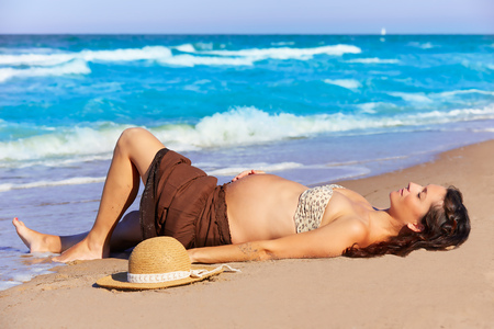 enceinte: Beautiful pregnant woman on the beach lying on sand